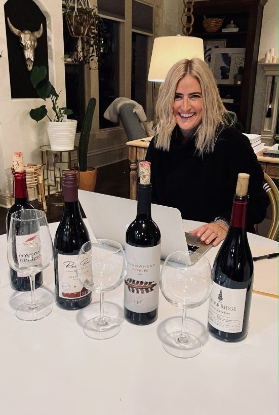 Andrea Larson sitting at a table with four wines to taste