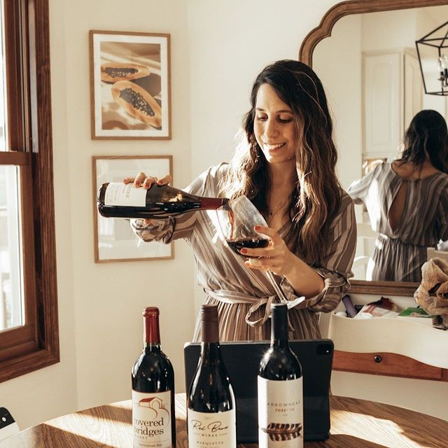 Gabriele Loomis pours a glass of wine in her dining room