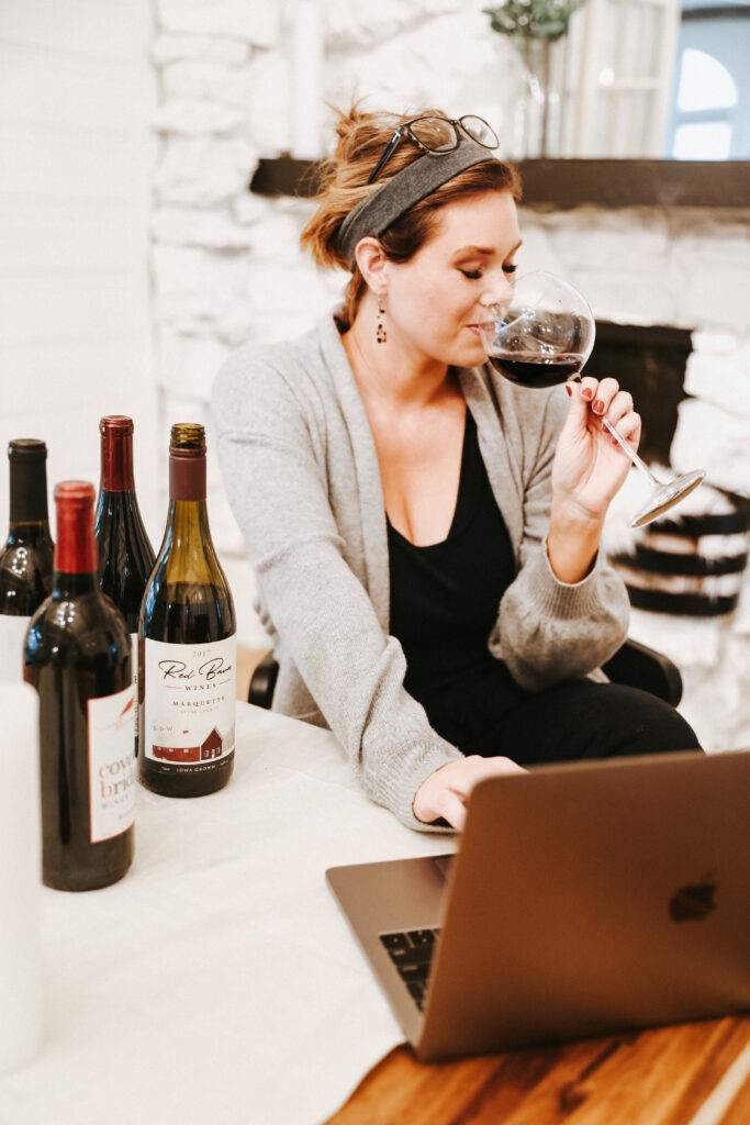 Sara Ayesh sips wine while delivering a virtual tasting event